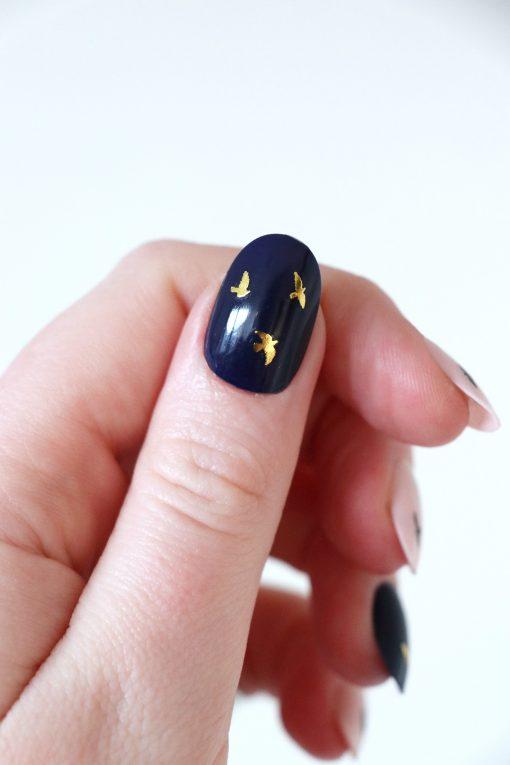 Gold and black flying bird nail tattoos